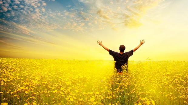 uomo a braccia alzate in un campo