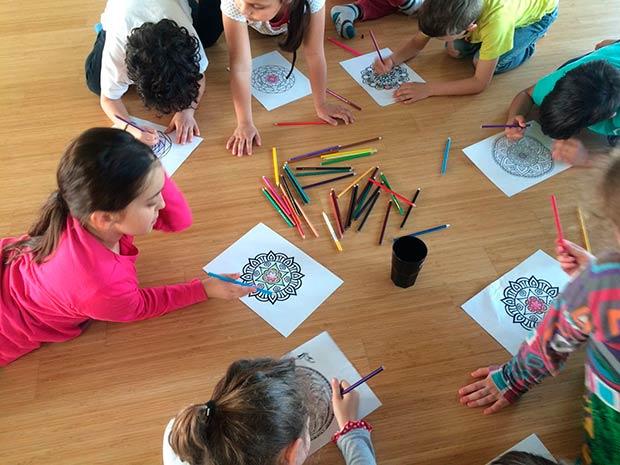 bambini che disegnano a lezione di yoga