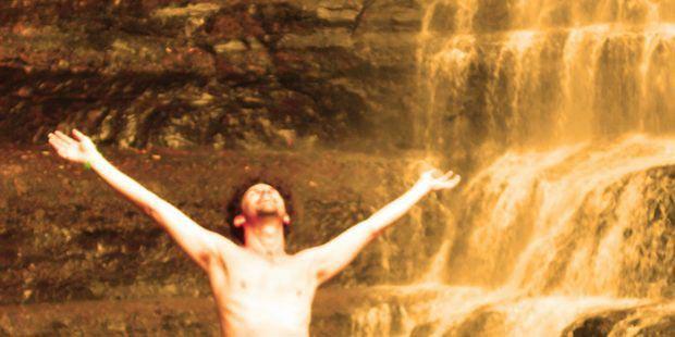 braccia sollevate di fronte a una cascata